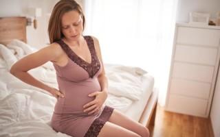 Почему болит поясница при беременности во втором триместре?